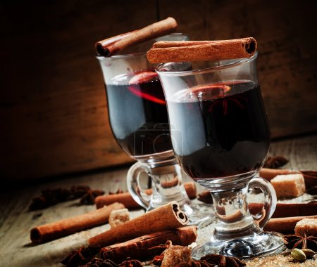 Hot mulled wine with spices on an old wooden background