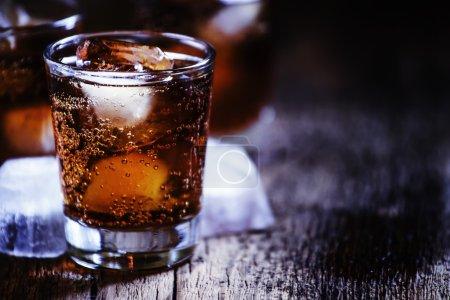 Photo pour Cocktail alcoolisé cola bourbon au whisky et glaçons, fond bois vintage, mise au point sélective - image libre de droit