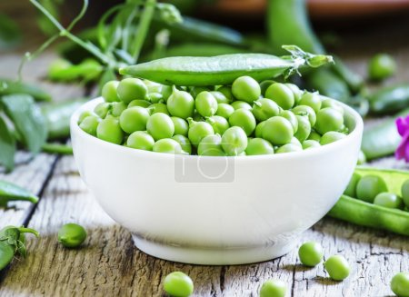 Peeled green peas in a white porcelain bowl