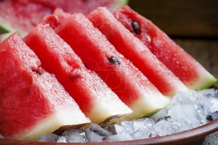 Watermelon slices with ice on a clay plate