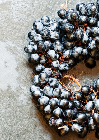 Blue grapes on old wooden background