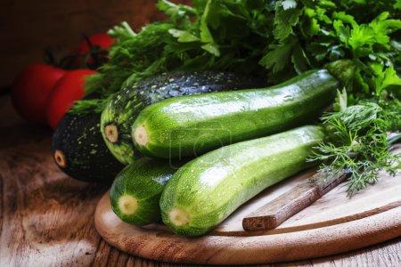Green zucchini on the wooden cutting board