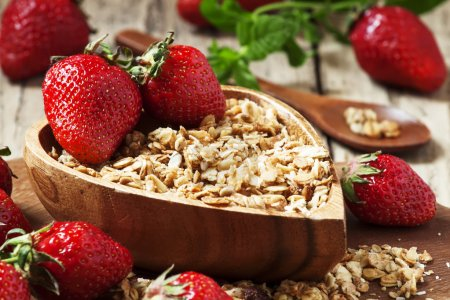 Homemade baked muesli with fresh strawberries and mint