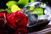 Sklenice červeného vína a kytice rudých růží