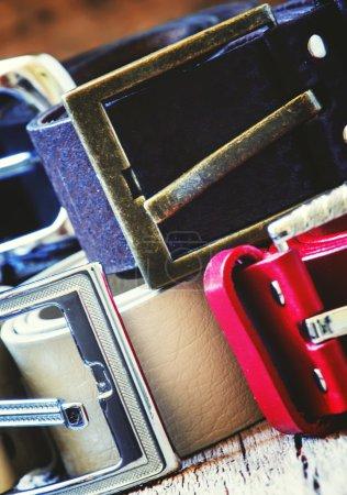 Stack of  belts, vintage wooden background