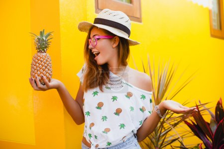 Young stylish woman holding pineapple