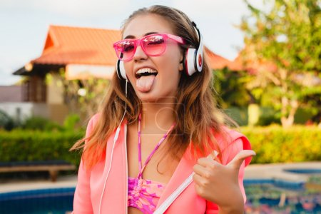 Photo for Young beautiful woman in headphones listening music. Funny happy girl in pink sunglasses - Royalty Free Image