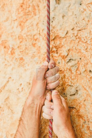 Photo for Hands holding rope on rock background - Royalty Free Image
