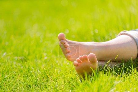 female bare feet on grass