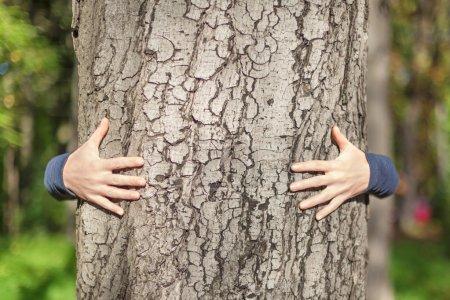 Photo pour Kid les mains en geste citoyen embrassant un tronc d'arbre - image libre de droit