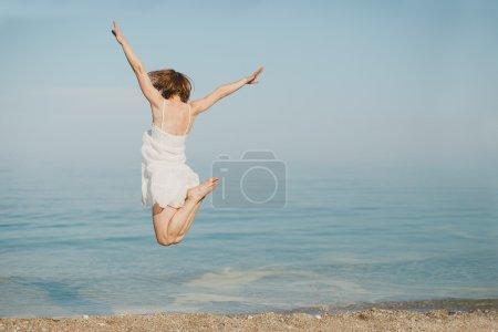 Photo pour Heureuse jeune femme en robe blanche pâle sautant sur la plage - image libre de droit