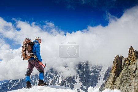 Mountaineer reaches the top of a mountain