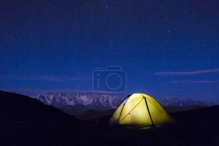 Photo pour Tente de camping jaune éclairée sous les étoiles la nuit - image libre de droit