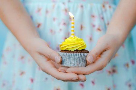 woman in blue dress holding birthday cupcake