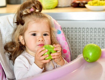 baby girl eating green apple