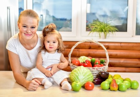 Happy young mother with a baby in the kitchen