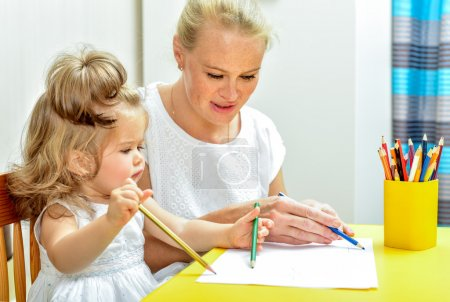 mother teaching daughter draw with pencils