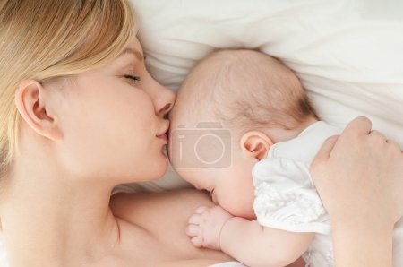 Young mother breastfeeds her baby