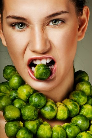 Photo for Beautiful woman with fresh Brussels sprouts. Professional makeup. Luxurious green necklace - Royalty Free Image