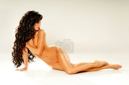 naked brunette with luxurious curly hair