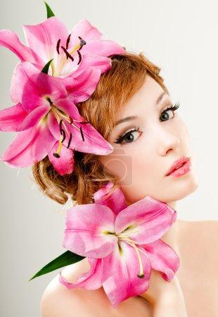 Photo pour Portrait de belle rousse fille avec des lis roses dans ses cheveux - image libre de droit