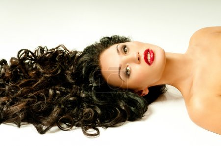 Brunette with curly hair and red lipstik...
