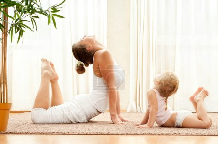 Mother and daughter doing yoga exercises