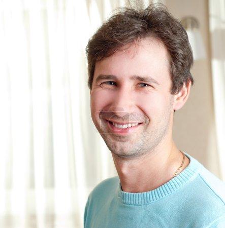 Photo pour Jeune homme souriant à l'intérieur - image libre de droit