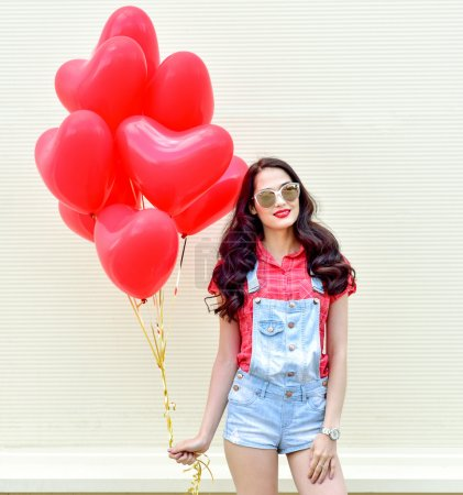 Woman with red heart balloons