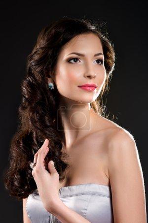 Photo pour Portrait glamour de jeune belle femme de la mode posant dans des accessoires de bijoux exlcusive. Maquillage professionnel et coiffure. Mode fille brune sur fond gris foncé. Concentre-toi sur les yeux . - image libre de droit