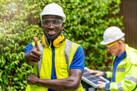 Photo for Factory worker technician engineer man standing confidence with green working suite dress and safety helmet in front worker checking solar cell panel for sustainable technology. - Royalty Free Image