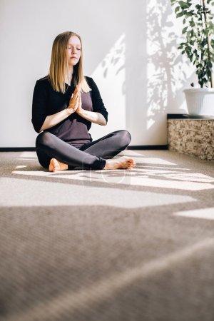 Photo pour Jeune fille cheveux blonds assis sur le sol dans la pose de méditation - image libre de droit