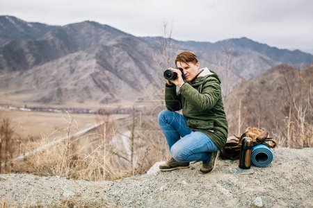 Man with a camera on the background of mountains