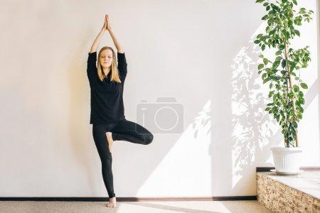 Photo pour Jeune femme faisant l'asana dans un studio de yoga. la pose de l'arbre - image libre de droit