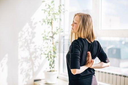 Photo pour Jeune fille blonde près de la fenêtre faisant de la méditation, les mains en namaste derrière le dos - image libre de droit