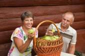 Coppie anziane felici con ricco raccolto di questanno. Coppie maggiori felici con un cestino di pere contro una parete di legno della casa