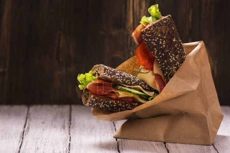 Photo for Rye bread sandwiches with ham, cheese and vegetables in a craft paper bag. Take away food. Selective focus - Royalty Free Image