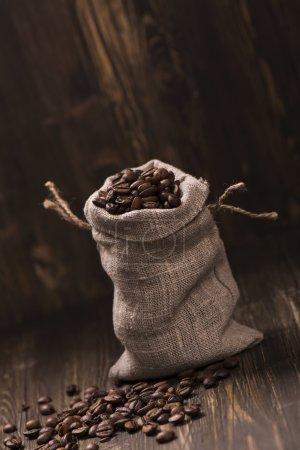 Grains de café dans des sacs de toile de jute sur fond en bois