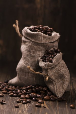 Coffee beans in burlap bags over wooden background