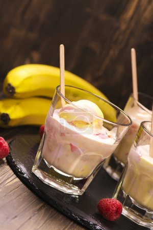 Refreshing milk cocktail with ice cream scoops, raspberry and banana