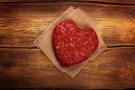 Photo for Raw heart shaped burger cutlet over grunge wooden background. Toned image. Top view - Royalty Free Image