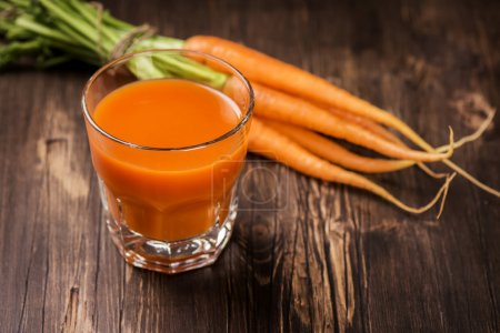 Photo for Glass of fresh-squeezed carrot juice and organic carrot on old rustic table - Royalty Free Image