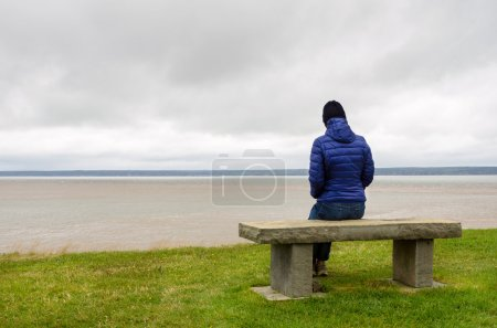 Photo for Photo of a Lonely woman sitting on a bench on the top of a cliff on a cold cloudy autumn day. Concept of loneliness. - Royalty Free Image