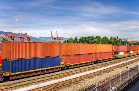 Photo pour Train chargé de conteneurs colorés dans un terminal de fret par une journée partiellement nuageuse - image libre de droit