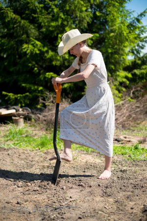 girl in a cowboy hat with a shovel digging a hole