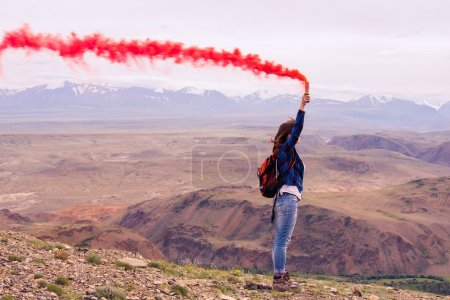 Girl with red smoke on the mountain