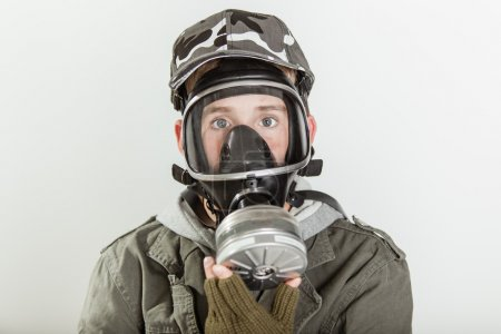 Male teen with face covered by respirator
