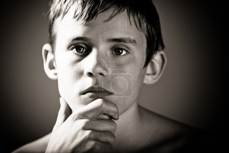 Photo for Black and White Head and Shoulder Portrait of Young Shirtless Teenage Boy Staring with Serious Expression Off Camera with Hand Resting on Chin in Studio with Dark Vignette Lighting and Copy Space - Royalty Free Image