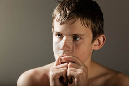 Thoughtful Boy with Hands in front of Mouth