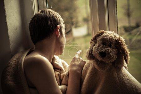 Photo pour Jeune adolescent enveloppé dans couverture confortable assis dans le rebord de la fenêtre avec le chien en peluche et scruter malheureusement Yard - image libre de droit